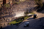 Santiago, Chile<br /> October 1988<br /> <br /> After General Pinochet lost a vote to remain in office, hundreds battle police demanding his immediate removal.<br /> <br /> In October 1988, General Augusto Pinochet ordered a plebiscite vote asking Chilean citizens whether he should continue in office. It produced a decisive &quot;no&quot; vote and the following year he lost the first presidential election in 19 years. However, under a constitution crafted by his advisors, he remained as army commander until 1998. <br /> <br /> Pinochet continued to wield enormous power until his arrest in London on human rights charges in October 1998.