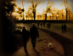 Two figures walking a small dog through a park in the evening