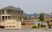 Western-style modern gated housing development with security guard and barriers, Yichang, China