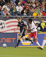 New England Revolution forward Zak Boggs (33) prepares to cross the ball after eluding New York Red Bulls defender Roy Miller (7). The New England Revolution defeated the New York Red Bulls, 3-2, at Gillette Stadium on May 29, 2010.