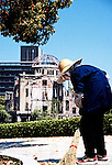 An elderly lady sweeps up fallen leaves near the A-Bomb Dome in Hiroshima, Japan.