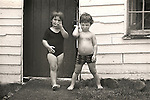 Boy, Girl Toddlers in front of shed. 1975