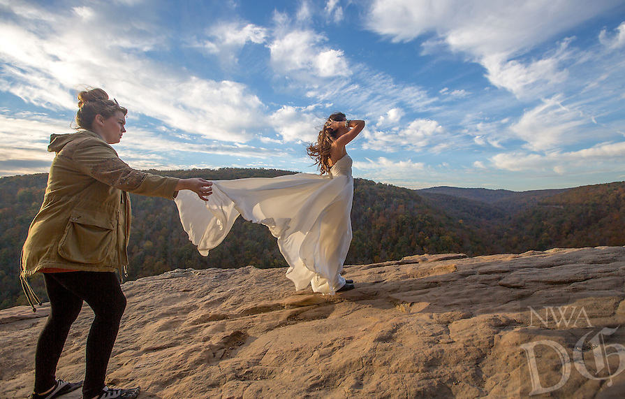NWA Media/JASON IVESTER --10/27/2014--<br /> Farron (cq) Martin, marketing manager for She Said Yes Bridal in Rogers, helps drape the bridal gown worn by model Laura Finn (cq) of Kansas City on Monday, Oct. 27, 2014, at Hawksbill Crag/Whitaker Point in the Ozark National Forest. The group was doing a style photo shoot with photographer Anna Hutchison for the boutique.