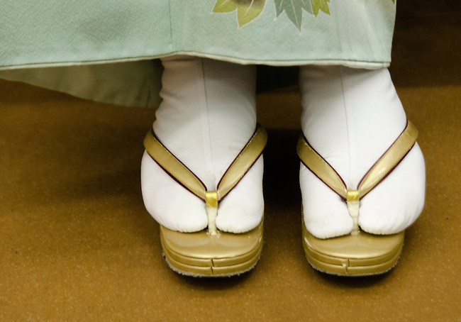 The feet of a Japanese women in kimono in her tabi socks and sandals.