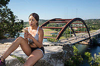 Beautiful African-American athlete woman texting messages on a smartphone outdoors on a cliff overlooking the 360 Bridge on Lake Austin, Texas