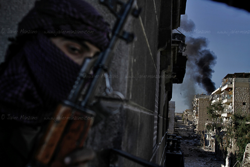 A Free Syria Army soldier surveys the effects of a rocket-propelled grenade (RPG) fired by a rebel soldier on a house allegedly populated by regime loyalists at the heavily contested neighborhood of Karmal Jabl in central Aleppo. This neighborhood has become one of the most contested flash points in the city due to it's proximity to a main road that connects the city from East to West. House-to-house combat has become the norm in this neighborhood as most of it's civilian population has fled. .October 18, 2012...© Javier Manzano..A Free Syria Army soldier looks at the effects of an RPG fired by a rebel soldier on a house allegedly populated by regime loyalists at the heavily contested neighborhood of Karmal Jabl in central Aleppo. This neighborhood has become one of the most contested flash points in the city due to it's proximity to a main road that connects the city from East to West. House-to-house combat has become the norm in this neighborhood as most of it's civilian population has fled. .October 18, 2012...© Javier Manzano..
