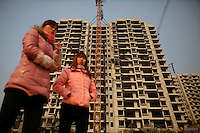 Migrant workers stand in front of a building at the construction site of Changxiang Gardens development complex in Fengrun District, Tangshan City, Hebei province, China January 28, 2016. REUTERS/Damir Sagolj