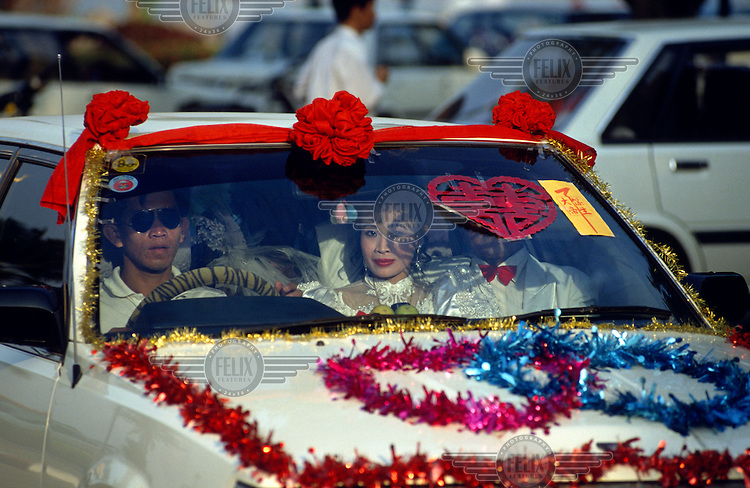 Newly weds sitting together in the front seat of a car decorated for the occasion, with hearts and the Chinese symbol for marriage - double happiness.