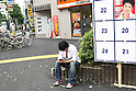 June 25, 2010 - Tokyo, Japan - A man seats beside the candidates posters during the Upper House election in Tokyo, Japan, on June 25, 2010. A July 2-4 survey by the Sankei newspaper showed that the DPJ may win between 48 and 55 of the 121 seats up for grabs in the 242-member upper house.