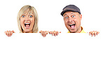 Young couple, man and woman faces with surprise scream, looking out from behind a blank white sign. Isolated on white background.