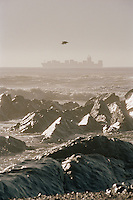 Rocky and rough coastline at Cape Town, with a large container ship on the horizon. Cape Town, South Africa