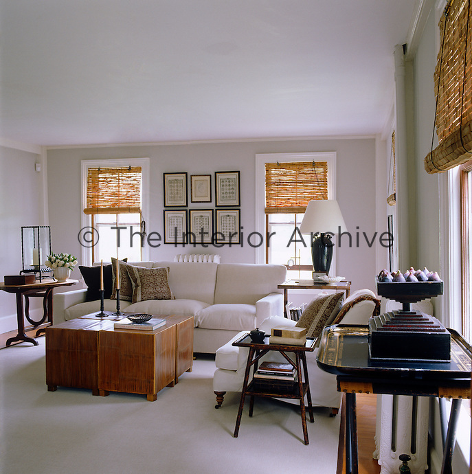 The comfortable living room has a black and white colour scheme and bamboo roller blinds