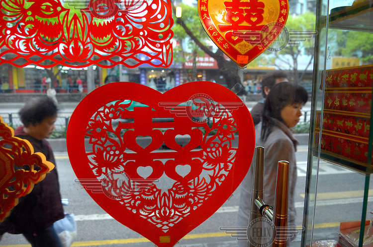 Window display of a shop selling decorations for marriages, showing heart shaped cut out representation of the characters used in Chinese to denote celebration and specifically marriage: 'double happiness', at the city's wedding dress market in the south of the city.