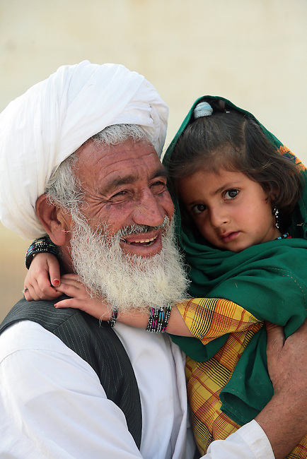 A man smiles and holds his daughter while being questioned by U.S. soldiers about recent Taliban attacks near the village of Zangabad in Panjwayi district, Kandahar province, Afghanistan. April 28, 2009. DREW BROWN/STARS AND STRIPES