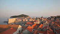 View over the rooftops of the medieval walled city with the old harbour on the left and Lokrum island behind, Dubrovnik, Croatia. The city developed as an important port in the 15th and 16th centuries and has had a multicultural history, allied to the Romans, Ostrogoths, Byzantines, Ancona, Hungary and the Ottomans. In 1979 the city was listed as a UNESCO World Heritage Site. Picture by Manuel Cohen