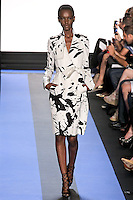 Herieth walks runway in a chalk white splatter print faille trench coat, by Monique Lhuillier, from the Monique Lhuillier Spring 2012 collection fashion show, during Mercedes-Benz Fashion Week Spring 2012.