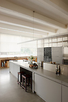 At the end of the long kitchen island an area has been reserved as a painting-cum-studio space and is lit by a long bank of windows veiled with white roller blinds