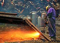 Man Cutting Railroad Rails with Cutting Torch, NJ. New Jersey USA junk yard.
