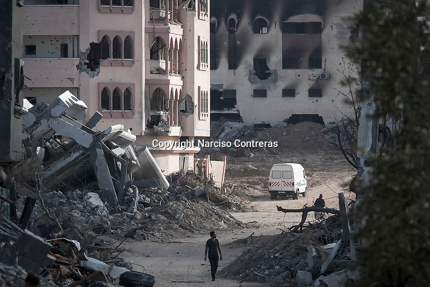 """In this Friday, Aug. 15, 2014 photo, a Palestinian man walk by house buildings destroyed by israeli airstrikes and artillery shelling during the """"Protective Edge"""" military operation in Shayaja neighborhood in Gaza City. After a five days truce was declared on 13th August between Hamas and Israel, civilian population went back to what remains from their houses and goods in Gaza Strip. (Photo/Narciso Contreras)"""
