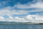 Rakiraki, Viti Levu, Fiji; the mountains across the bay from Volivoli Beach Resort with late afternoon clouds and blue sky above