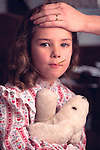 mother's hand feeling for fever on forehead of young girl in pajamas with thermometer in mouth holding teddy bear