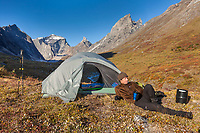 Man reclines at a beautiful campsite in the Arrigetch Peaks, Gates of the Arctic National Park, Alaska.