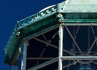 """A highly-cropped detail view of my """"Old Point Loma: towering lantern room"""" image.  This crop shows the beautiful details of the construction of the lantern room's room, including lion or gargoyle figureheads at each of the roof's 10 corners, and a vertical cut-out portion of metal above each window.  This cut out patterns appears to be made to look like a series of waves heading towards each other, with the cutouts themselves appearing to be horns.   The lighthouse is in Cabrillo National Monument near San Diego, CA.  As this is a severe crop, this image is not suitable to be printed exceptionally large (maybe up to 8 or 10"""" wide?), though the image it comes from can probably be printed up to 20""""x30""""."""