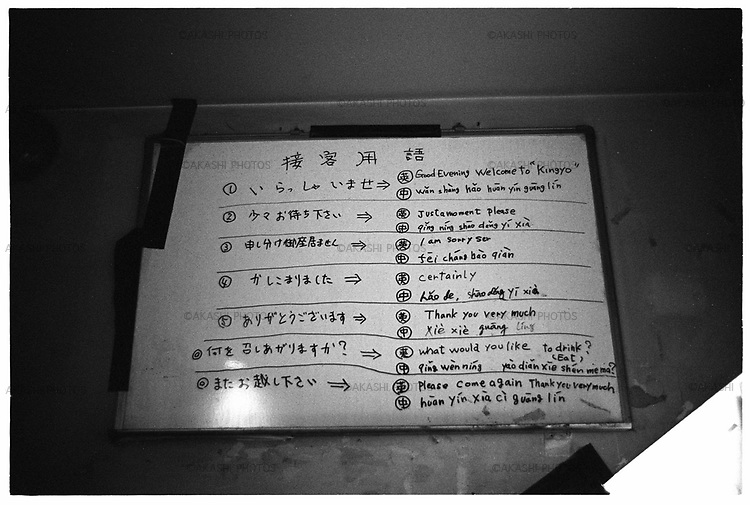 Phrases written in Chinese and English for Chinese and English speaking customers in a kitchen in Kingyo,transsexual show bar, in Roppongi, Tokyo, Japan.