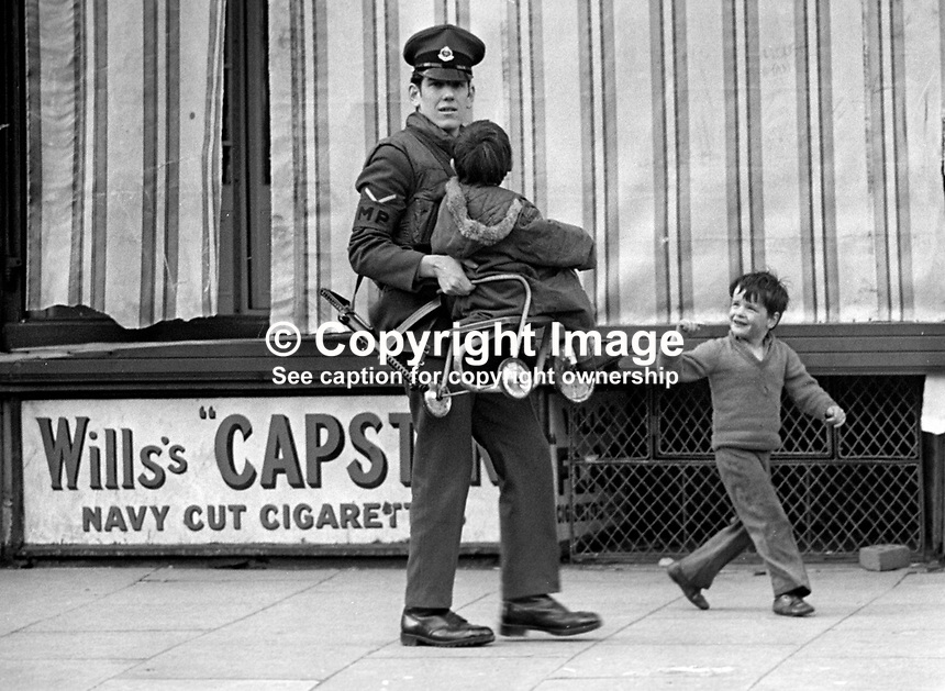 British Army Military Policeman carries a child and its tricycle away from danger following an explosion at a Co-operative Store, Belfast, N Ireland, UK. A second child is also escorted away. A second bomb at the store was subsequently defused. NI Troubles.  Ref: 19720300001.<br />