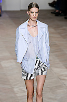 Julia Frauche walks the runway in a blue/white multi-striped cotton motorcycle jacket, blue/white striped silk button-down tank top, and navy/white striped denim shorts, by Tommy Hilfiger for the Tommy Hilfiger Spring 2012 Pop Prep Collection, during Mercedes-Benz Fashion Week Spring 2012.