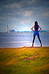 Woman at quayside looking over estuary to Power station