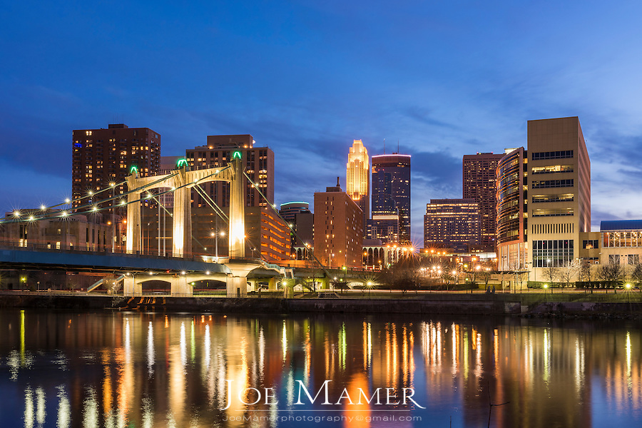 Minneapolis skyline at dusk with the Mississippi River and Hennepin Avenue bridge in the foreground. The Mississippi River through the Twin Cities is part of the Mississippi National River & Recreation Area.