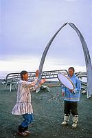 Native Alaska dancers, Bowhead whale bone arches and umiak (whale boat) skeletons, Arctic ocean beach, Utqiagvik (Barrow), Alaska
