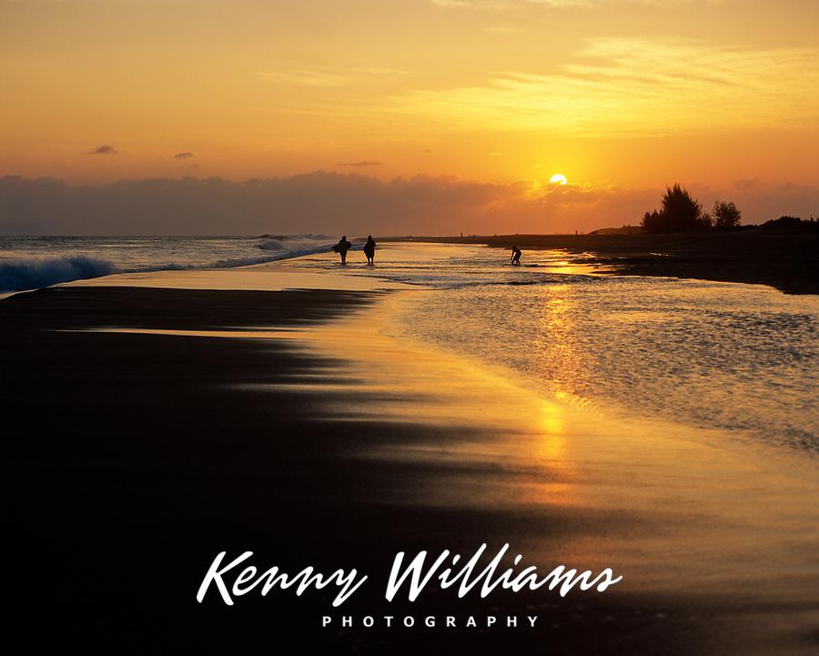Skimboarders Playing in Surf at Sunset, Kekaha Beach, Kauai, Hawaii, USA.