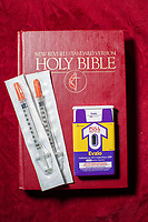 "A sterile syringe, a Narcan (Naloxone) injector and a Bible on a pew at Green Street Church in Winston-Salem, NC, which houses The Twin City Harm Reduction Collective, a needle exchange for addicts. Narcan blocks and reverses the effects of heroin and other opioids and has saved countless people from overdose deaths. Colin Miller, a recovering addict and one of the collective's founders, cites Jesus' words in Matthew 25:40 as a motivation to help addicts use drugs in a less harmful way, and ultimately become sober: ""Truly, I say to you, as you did it to one of the least of these my brothers, you did it to me.""  (Justin Cook)"
