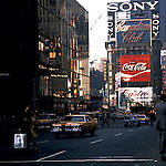 Shoppers and traffic and the neon advertising hoardings that are reflected in Manhattan office windows, Broadway, Times square, Manhattan, New York, USA circa 1975