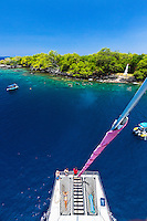 Tourists on a catamaran cruise marvel at the clear waters of Kealakekua Bay, Hawai'i Island.