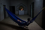 """A young boy in rests in a hammock in San Dionisio...The Isthmus of Tehuantapec, long a center for indigenous land ownership, is now embroiled in a land dispute over wind farm land...Called """"Mexico's little waist,"""" the Isthmus is a wind tunnel that links the Gulf of Mexico to the Pacific through mountain passes at the narrowest part of Mexico. The geographical funnel makes it one of the windiest places in North America and for a decade wind energy companies have been jostling to acquire land to power the likes of Coca-Cola and Wal Mart."""