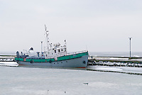 Lithuanian fishing boat frozen in sea ice, Curronean lagoon, Lithuania