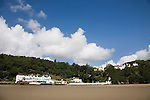 "Portmeirion, in North Wales, is a resort, where no one has ever lived. A self-taught Welsh architect named Sir Clough Williams-Ellis built it out of architectural salvage between the 1920s and 1970s, loosely based on his memories of trips to Portofino. Including a pagoda-shaped Chinoiserie gazebo, some Gothic obelisks, eucalyptus groves, a crenellated castle, a Mediterranean bell tower, a Jacobean town hall, and an Art Deco cylindrical watchtower. He kept improving Portmeirion until his death in 1978, age 94. It faces an estuary where at low tide one can walk across the sands and look out to sea. At high tide, the sea is lapping onto the shores. Every building in the village is either a shop, restaurant, hotel or self-catering accomodation. The village is booked out at high season, with numerous wedding receptions at the weekends. Very popular amongst the English and Welsh holidaymakers. Many who return to the same abode season after season. Hundreds of tourists visit every day, walking around the ornamental gardens, cobblestone paths, and shopping, eating ice-creams, or walking along the woodland and coastal paths, amongst a colourful assortment of hydrangea, rhododendrons, tree ferns and redwoods. The resort boasts two high class hotels, a la carte menus, a swimming pool, a lifesize concrete boat, topiary, pools and wishing wells. The creator describes the resort as ""a home for fallen buildings,"" and its ragged skyline and playful narrow passageways which were meant to provide ""more fun for more people."" It does just that.///Portmeirion Hotel overlooking the estuary Afon Dwyryd towards Porthmadog and Tremadog. View from estuary. Portmeirion village up on hill."