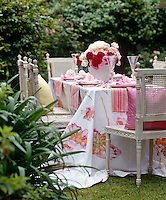 The table is dressed with a beautiful floral cloth and striped pink place mats