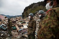 Members of the Japanese Self Defence Force (SDF) watch rescue operations. Thousands of people died in this small town which ran out of body bags. On 11 March 2011 a magnitude 9 earthquake struck 130 km off the coast of Northern Japan causing a massive Tsunami that swept across the coast of Northern Honshu. The earthquake and tsunami caused extensive damage and loss of life.