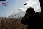 A tourist takes a photos of Mt Fuji on a bus taking travelers to the Asagiri Plateau and beyond in Shizuoka Prefecture Japan on 22 March 2013.  Photographer: Robert Gilhooly