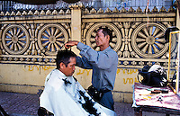 Like a shoe shine, the barbar is a common sight all over the world. For a $1 he will cut your hair at his sidewalk stall that packs into a suitcase. Nikon F80. 2004