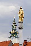 Die goldene Marienstatue des Madonnenbrunnens. Im Hintergrund die Marienkirche. / The golden statue of the Virgin Mary fountain. St. Mary's Church in the background.