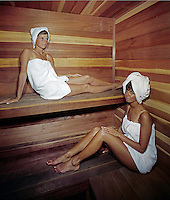Young women wrapped in towels enjoying the motel sauna.
