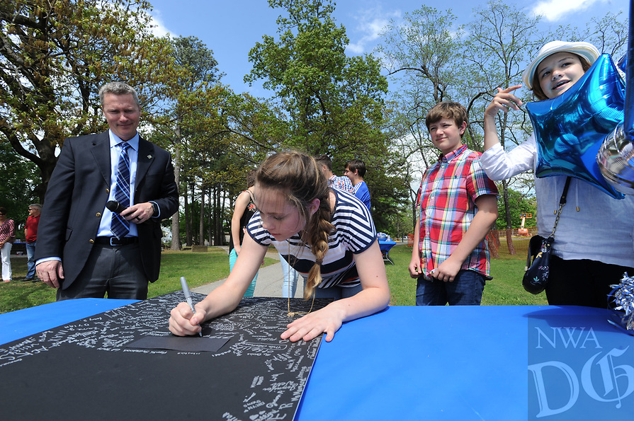 NWA Democrat-Gazette/ANDY SHUPE<br /> Dennis Chapman (left), president and head of school at The New School, watches Wednesday, April 19, 2017, as Reagan McGurk (center), 14, a ninth-grader at the school, joins other students in signing a piece of mat board during a beam raising and tour of the school's expansion project in Fayetteville. The New School hopes to open the facility in the fall for the 2017-18 school year.