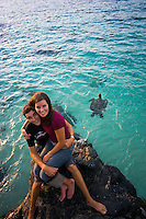 Young woman sits on the lap of a young man at Waimea bay. Turtle swims by in the background.