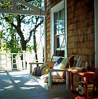 A swinging seat hangs from the struts of the covered porch that runs around the outside of this shingled country house