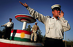 At a roundabout bearing the Kurdish flag on the outskirts of Suleymaniah, Iraqi Kurdistan on Tues. September 19, 2006 an unarmed policeman guides morning traffic entering the city. The site of an unarmed policeman in the cities of the south would be unthinkable where the insurgency has claimed the lives of thousands of police officers.